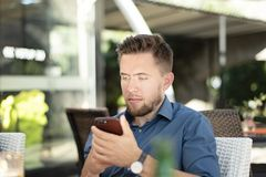 Oung handsome man looking at his mobile phone royalty free stock photo