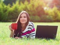 Oung kopplar av den trendiga kvinnan, efter arbete med bärbara datorn i stad har parkerat royaltyfri fotografi