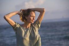 Oung lycklig härlig och glamorös blond kvinna som så poserar på stranden som bär den stilfulla klänningen som ler ny gladlynt kän arkivfoto