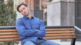 Oung Man Sleeping while Sitting Outdoor on Bench. Young Man Sleeping while Sitting Outdoor on Bench, 4k high quality, 4k high quality stock footage