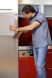 oung Mann, der im Kühlschrank schaut Stockbild