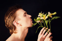 Oung men sniffing bouquet of flowers Royalty Free Stock Photo