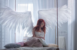 Oung model with open angel wings and pink dress sitting on hanging bed Stock Image