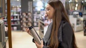 Oung mooie vrouw die thermosflessenfles in een opslag kiezen supermarke stock videobeelden