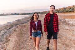Oung par på stranden som tillsammans går arkivbild