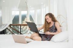 Oung piękna caucasian kobieta kłaść na łóżku i używa laptop Fotografia Royalty Free