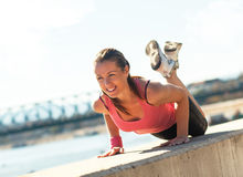 Oung sporty woman doing push-ups. Young sporty woman doing push-ups in sunny day on riverbank Royalty Free Stock Photography