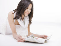Oung teen girl in white dress reading on floor Royalty Free Stock Images