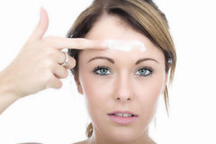 Oung Woman Applying Moisturizing Cream to Forehead Face Stock Image