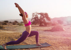 Oung woman doing yoga in desert at sunrise time. Happy traveller relax during trip in Israel desert Stock Photos