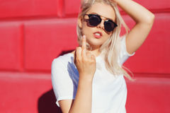 Oung woman insulting with middle finger. Shallow DOF. Focus on finger. young woman insulting with middle finger over red background Stock Image
