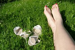 Oung woman with long legs sits in a meadow Stock Photos