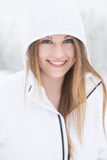 Oung woman smiling with hood up standing in snow. Young woman outdoors hiking during a winter snow storm Royalty Free Stock Photo