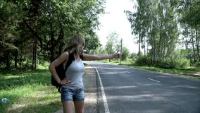 Oung woman traveler with backpack hitchhiking on road. Hitchhiking woman with backpack walking on road. Cute woman with backpack and sunglasses hitch hiking on stock video