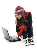Oung woman in winter clothes working on laptop Stock Photography