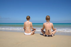 Oung women meditating on the tropical beach Royalty Free Stock Image