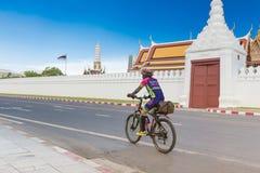 Oungman sta guidando una bici sulla via intorno al palazzo tailandese immagine stock libera da diritti
