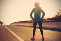 Oungs-Frauenläufer in der Sportkleidung, die mit ihren Händen auf Hüften auf Sonnenaufgangstraße steht Stockbilder