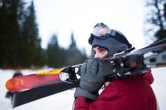 Oungs-Mann, der Ski hält Skifahrer, der die Skis betrachten die Berge hält Seitenansicht des hübschen Skifahrermannes mit Maske u Lizenzfreie Stockfotografie