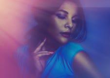 Oungvrouw die blauwe kleding met de lichten van de dansclub dragen Stock Fotografie