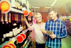 сouple of customers purchasing at wine section in supermarket. Happy american сouple of customers purchasing at wine section in supermarket Royalty Free Stock Photography
