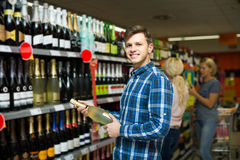 сouple of customers purchasing at wine section in supermarket Stock Photos