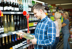 сouple of customers purchasing at wine section in supermarket Royalty Free Stock Image