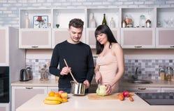Ouple de ¡ de Ð préparant la nourriture dans la cuisine Femme enceinte images stock