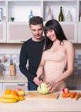 Ouple de ¡ de Ð préparant la nourriture dans la cuisine Futurs parents image libre de droits