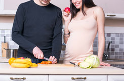 Ouple del ¡ di Ð che prepara alimento nella cucina Donna incinta immagini stock