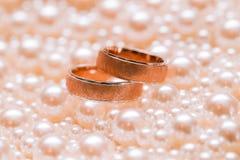 Ouple do ¡ de Ð das alianças de casamento do ouro em scatterings das pérolas casamento Fotografia de Stock