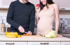Ouple do ¡ de Ð que prepara o alimento na cozinha Mulher gravida imagens de stock
