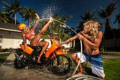 Ouple do ¡ de Ð que tem o divertimento com a mangueira de jardim que espirra a chuva do verão Imagens de Stock