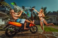 Ouple do ¡ de Ð que tem o divertimento com a mangueira de jardim que espirra a chuva do verão Imagens de Stock Royalty Free