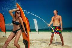 Ouple do ¡ de Ð que tem o divertimento com a mangueira que espirra a chuva do verão Foto de Stock Royalty Free