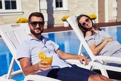 Сouple enjoying sun in modern residence near pool Royalty Free Stock Photo