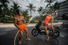Сouple having fun with garden hose splashing summer rain Stock Photo