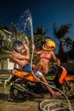 Сouple having fun with garden hose splashing summer rain Royalty Free Stock Images