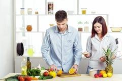 Ouple heureux de c dans l'amour dans la cuisine faisant le jus sain à partir de l'orange fraîche Photographie stock libre de droits