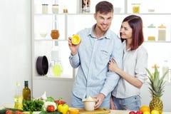 Ouple heureux de c dans l'amour dans la cuisine faisant le jus sain à partir de l'orange fraîche Photos libres de droits