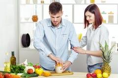 Ouple heureux de c dans l'amour dans la cuisine faisant le jus sain à partir de l'orange fraîche Image stock