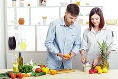 Ouple heureux de c dans l'amour dans la cuisine faisant le jus sain à partir de l'orange fraîche Images stock