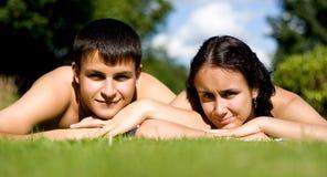 Ouple heureux se trouvant sur l'herbe. Images stock