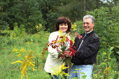 Сouple holding bouquet from autumn leaves. Senior couple holding bouquet from autumn leaves Stock Photos