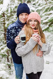 Ouple with hot drinks in cups in forest among fir trees Royalty Free Stock Images