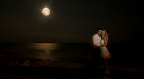 Сouple kissing at the beach under moonlight Royalty Free Stock Photo