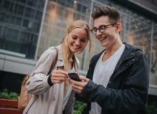 Ouple o risa de los amigos divertida y divertirse con un teléfono elegante en una calle grande de la ciudad Fotografía de archivo libre de regalías