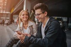 Ouple o risa de los amigos divertida y divertirse con un teléfono elegante en una calle grande de la ciudad Imagen de archivo libre de regalías