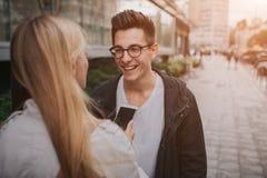 Ouple o risa de los amigos divertida y divertirse con un teléfono elegante en una calle grande de la ciudad Imágenes de archivo libres de regalías
