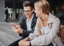 Ouple ou rire d'amis drôle et avoir l'amusement avec un téléphone intelligent dans une grande rue de ville photographie stock libre de droits